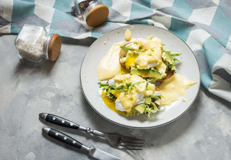 Eggs Benedict with salad and avocado on concrete background. Banque d'images