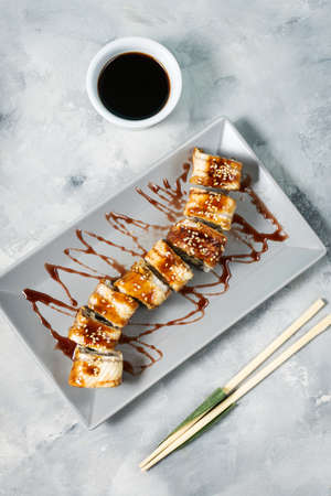 Golden dragon sushi roll with tuna, eel, cucumber served on concrete background. Top view Stockfoto