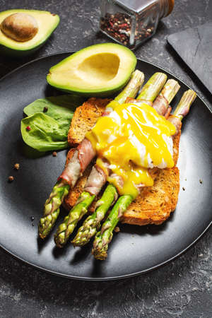 Grilled green asparagus wrapped with bacon, benedict poached egg and avocado on toasts Reklamní fotografie