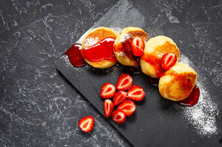 Russian syrniki or cottage cheese fritters or pancakes served with strawberry on black stone background. Top view