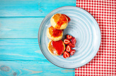 Russian syrniki or cottage cheese fritters or pancakes served with strawberry on blue wood background. Top view
