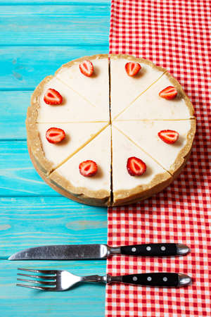 Homemade cheesecake with fresh strawberries sliced on blue wooden background