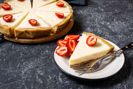 Homemade cheesecake with fresh strawberries sliced on black stone background