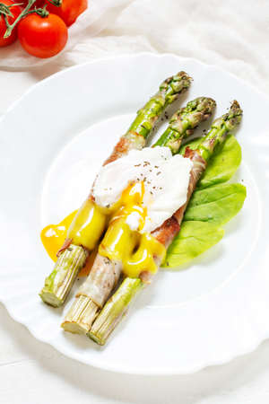 Grilled green asparagus wrapped with bacon, benedict poached egg on white wood background.