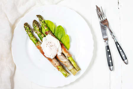 Grilled green asparagus wrapped with bacon, benedict poached egg on white wood background. Breakfast