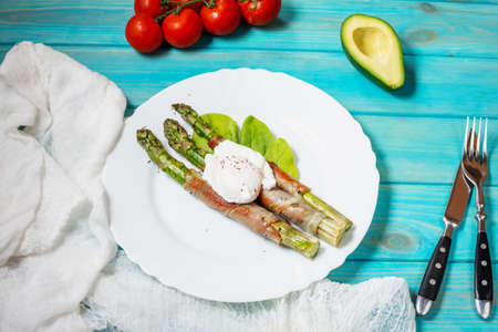Grilled green asparagus wrapped with bacon, benedict poached egg on blue wood background. Stok Fotoğraf
