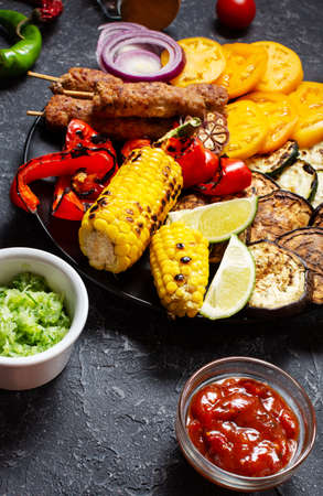 Assorted delicious grilled vegetables and meat on a dark stone background. Summer food barbecue. Stok Fotoğraf
