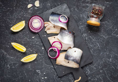 Herring fillet with salt, herbs, onion and lemon on black plate on stone background. Top view. Healthy food