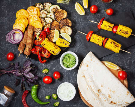 Assorted delicious grilled vegetables and meat on a dark stone background. Summer food barbecue. Top view