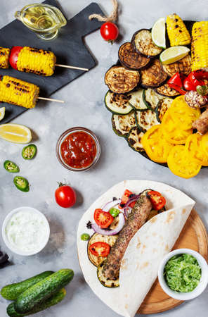 Assorted delicious grilled vegetables and doner kebab on a concrete background. Summer food barbecue. Top view Stok Fotoğraf