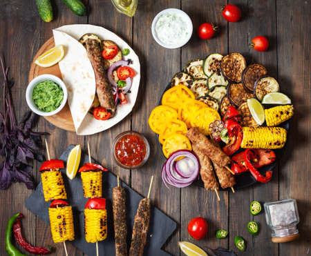 Assorted delicious grilled vegetables and doner kebab on a wooden background. Summer food barbecue. Top view