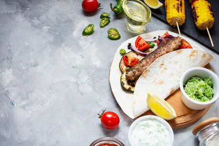 Assorted delicious grilled vegetables and doner kebab on a concrete background. Summer food barbecue. Copy space