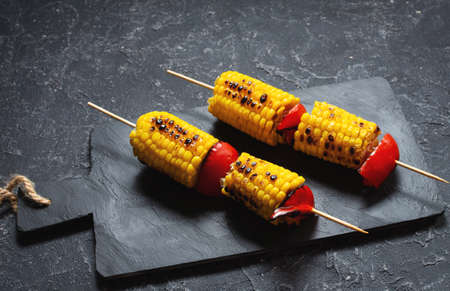 Grilled sweet corn on the sticks, black stone textured table