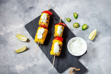 Grilled sweet corn on the sticks, concrete textured table