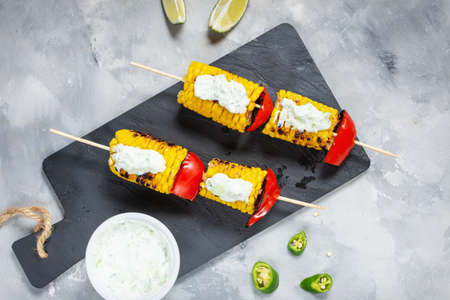 Grilled sweet corn on the sticks, concrete textured table. Top view Stok Fotoğraf