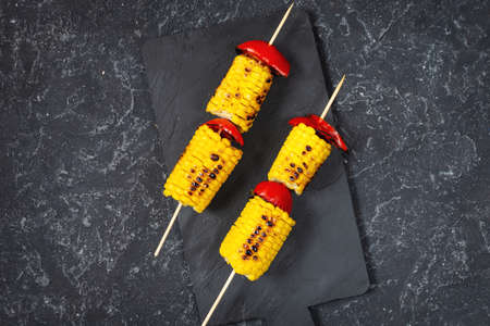 Grilled sweet corn on the sticks, black stone textured table, top view Stok Fotoğraf