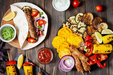 Assorted delicious grilled vegetables and doner kebab on a wooden background. Summer food barbecue. Stok Fotoğraf