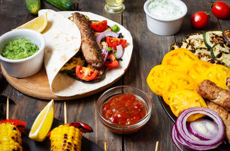 Assorted delicious grilled vegetables and doner kebab on a wooden background. Summer food.