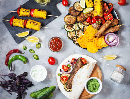 Assorted delicious grilled vegetables and doner kebab on a concrete background. Summer food barbecue. Stok Fotoğraf
