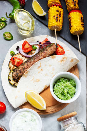 Assorted delicious grilled vegetables and doner kebab on a concrete background. Summer food