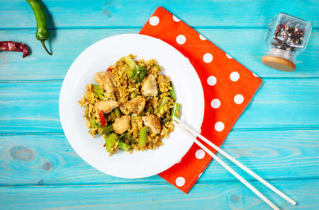 Rice with chicken meat and vegetables in a plate on blue wooden table. Top view