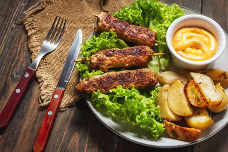 Grilled shish kebab served with fried potatoes and sauce on a wooden background Stock Photo