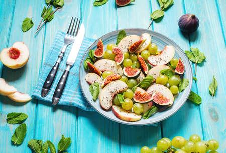 Frischer Obst- und Beerensalat mit Trauben, Feige und Pfirsich auf blauem Holzhintergrund. Gesundes Essen. Standard-Bild