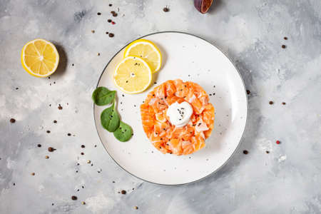 Delicious avocado and salted salmon tartar on concrete background. Top view Imagens