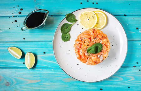 Delicious avocado and salted salmon tartar on blue wooden background. Top view Stock Photo
