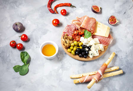 Italian antipasto with prosciutto, ham, cheese, olives and grissini breadsticks on concrete background. Top view