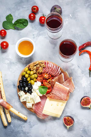 Italian antipasto on wooden cutting board with prosciutto, ham, cheese, olives and grissini breadsticks on concrete background. Top view