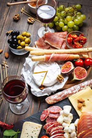 Italian antipasto with prosciutto, ham, cheese, olives and grissini breadsticks on rustic wooden background