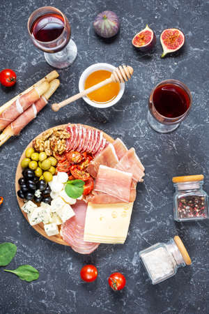 Italian antipasto on wooden cutting board with prosciutto, ham, cheese, olives and grissini breadsticks on black stone background. Top view Banco de Imagens