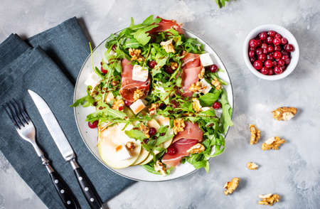 Green salad with arugula, pear, jamon and feta cheese on concrete background. Top view. Healthy food