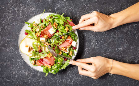 Green salad with arugula, pear, jamon and feta cheese on dark stone background. Female hands holds fork and knife. Top view. Healthy food