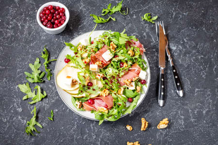 Green salad with arugula, pear, jamon and feta cheese on dark stone background. Top view. Healthy food 写真素材