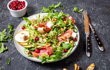 Green salad with arugula, pear, jamon and feta cheese on dark stone 写真素材