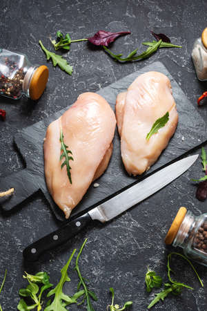 Fresh raw chicken fillet, spices and herbs on black stone background 版權商用圖片