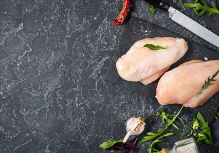 Fresh raw chicken fillet, spices and herbs on black stone background, top view and copy space