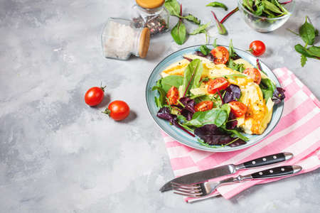 Herb omelette with cheese, cherry tomatoes and arugula on concrete background. Breakfast Imagens