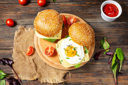 Breakfast two burgers with chicken, fried egg and cheese on a rustic wooden background