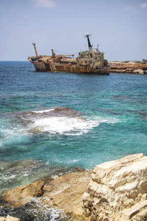 Paphos. Shipwreck. The ship crashed on the coastal rocks at the shore of the Mediterranean sea. Tourist attractions of Cyprus.