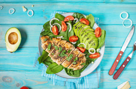 Grilled chicken and avocado salad with spinach and cherry tomatoes on blue wooden background. Healthy food, ketogenic diet, lunch concept. Top view