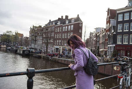Girl in the coat and backpack enjoying city. Young woman looking to the side on Amsterdam channel, Netherlands, Europe.