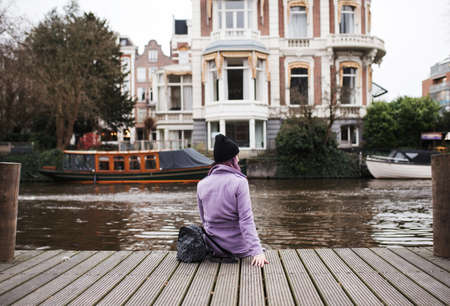 Back view of a woman watching the view of canal in Amsterdam. Vacation concept at Netherlands. 스톡 콘텐츠
