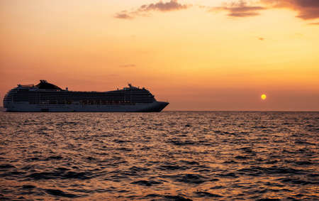 Cruise liner in open sea. Passenger ferry sailing at hot sunset