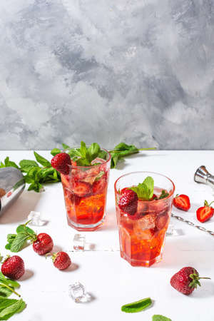 Strawberry mojito and ingredients on white wooden background
