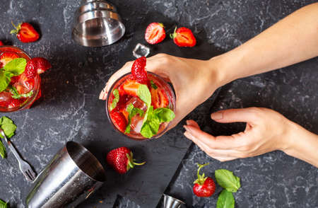 Female hands holds a glass of Strawberry mojito on black stone background. Top view