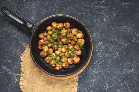 Delicious fried mushrooms in pan on black stone table, top view Banco de Imagens