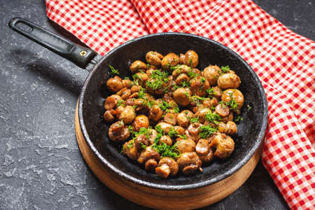 Delicious fried mushrooms in pan on black stone table